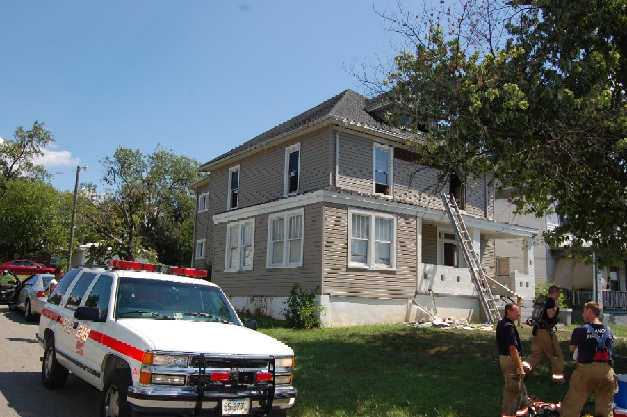 House with firemen standing outside and emergency fire vehicle.
