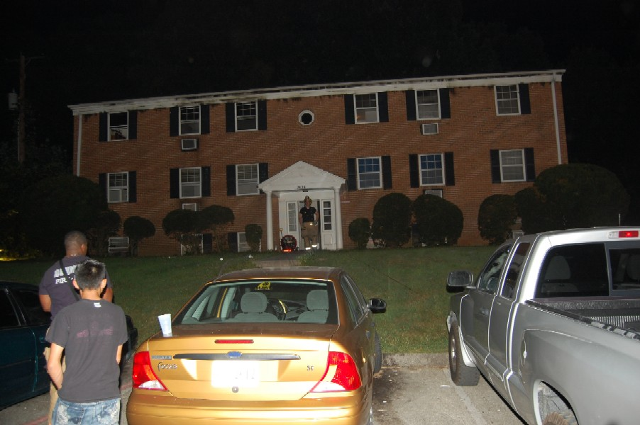 Large brick home being investigated at night.