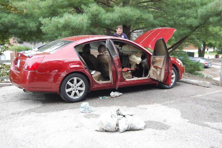 Red car with all the doors open and hood open while man investigates